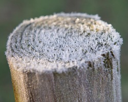 Closeup detail of wooden post top in garden covered with hoar frost ice during winter