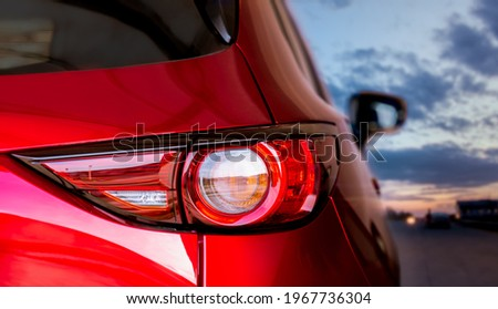 Closeup detail on modern design LED taillight of red crossover car. Exterior glossy automobile. View of vehicle backlight with blurred sunset background while road trip, depth of field. Stockfoto ©