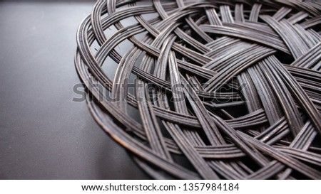 Closeup Detail Photograph of Natural Woven Rattan Bowl with Moody Dark Monochromatic Contrast Background #1357984184