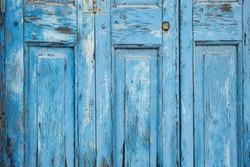Closeup detailed texture of bright blue paint peeling off of an old wooden door. Background texture is from a door in Mykonos, Greece.