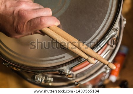 closeup detailed view of human person hands holding used drum sticks on old dusty snare drum background
