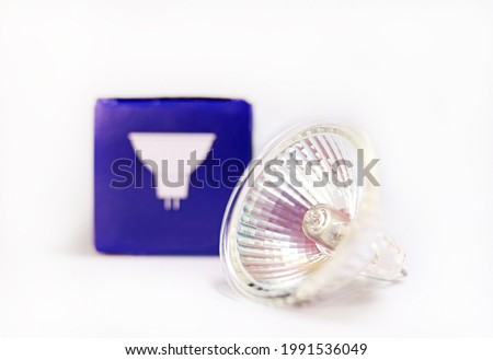 Closeup dichroic halogen lamp with its package on white background. Dichroic halogen lamp MR-16-50 GU5.3, dichroic reflector lamp, halogen bulb manufactured in China. Bright light beam