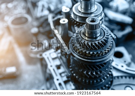Closeup disassembled car automatic transmission gear part on workbench at garage or repair factory station for fix service or maintenance. Vehicle part detail. Complex industrial mechanism background Foto stock ©