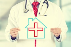 Closeup doctor hands holding white paper house with red cross sign isolated on hospital clinic office background. Retro instagram style filter image