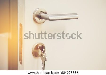 closeup Door lock keys, Real estate concept door handle, Key insert and hold in metallic knob on white door horizontal #684278332