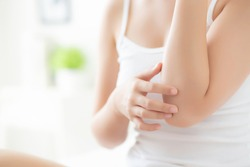 Closeup elbow of beautiful asian woman applying skincare and moisturizer cream or treatment for scratch and itchy, asia girl applying cream and lotion for dryness of skin care with cosmetic makeup.