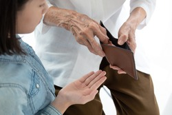 Closeup elderly woman hands open wallet,grandmother or guardian giving pocket money to granddaughter,asian little girl demanding money,parent pulls out money from wallet to give her