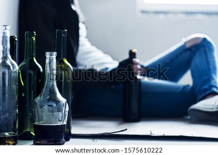 Closeup empty glass bottles. On background homeless drunk woman is sitting on cardboard on floor in abandoned house. Addicted teenage girl drunkard is drinking beer. Alcoholism, alcohol abuse concept. Сток-фото ©