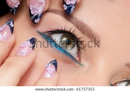 Closeup eyes make-up zone. Nail art. Finger.  Pink and blue color. High resolution.