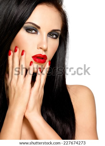 Closeup face of a beautiful brunette woman with red nails and lips - isolated on white background