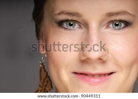 Closeup face of blue eyed girl on gray