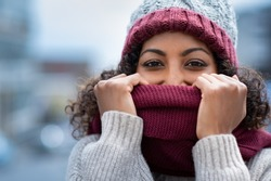 Closeup face of happy african girl holding woolen scarf with hands over nose to protect from the frost. Beautiful young woman in warm winter knitted clothes covering her face and looking at camera.