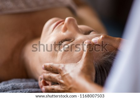Closeup face of mature woman having facial massage at spa. Senior woman lying at spa while a massage therapist doing anti-aging treatment. Masseur doing head massage at wellness center.