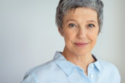 Closeup face of senior business woman standing against grey background with copy space. Portrait of successful woman in blue shirt feeling confident and looking at camera. Happy mature woman face.