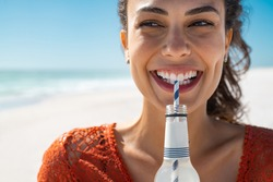 Closeup face of young woman drinking fresh sparkling water from a glass bottle at beach. Portrait of beautiful carefree girl drinking soft drink with straw during summer. Smiling girl staying hydrated