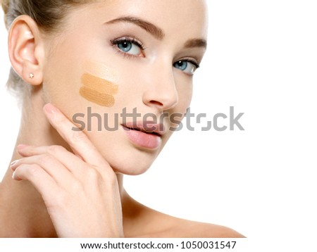 Closeup face of young woman with cosmetic foundation on skin. Beauty treatment concept. Girl makes makeup.
