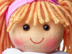 Closeup face rag doll smiling on a white background