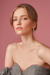 Closeup face studio portait of young elegant blonde caucasian woman with natural makeup and hairstyle wearing jewelry, earrings and posing against pink background. Fashion model