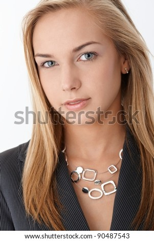 Closeup facial portrait of young smart businesswoman smiling at camera confidently.?