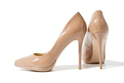 Closeup fashion high heels women shoes beige color isolated on white background. Top view. Stiletto shoe style in ladies wardrobe. High fashion and formal female accessory. Copy space. Selective focus