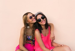 Closeup fashion lifestyle portrait of two pretty best friends girls, wearing bright swag style floral hats, mirrored sunglasses, having fun and make crazy funny faces. Two sisters posing on party.