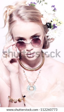 Closeup fashion portrait of beautiful teenager in jewelery flowers at hairstyle in pink glasses isolated