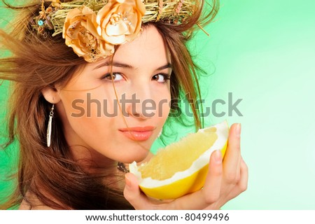 Closeup fashion portrait of pretty young woman wearing dress and headwear crown of hay and flower eating fresh pomelo fruit against beautiful green background. Freshness concept