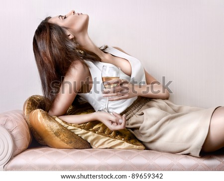 Closeup fashion portrait of young sexy hot woman sitting relaxed on comfortable luxury sofa in vintage interior and drinking champagne or wine