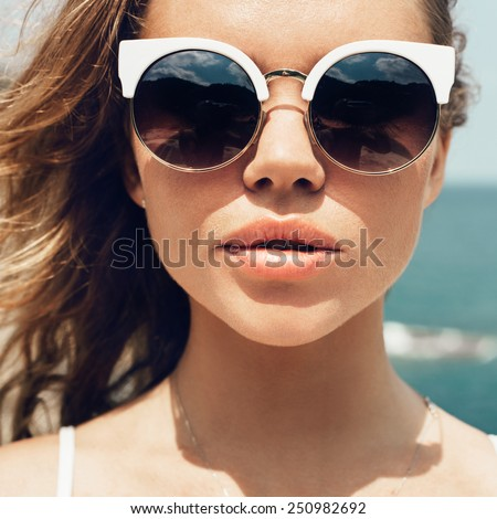 Closeup fashion summer portrait of pretty young woman in sunglasses posing on the beach on vacation