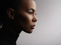Closeup fashionable portrait of a metis young woman with perfect smooth glowing skin, full lips, collected hair and long neck. Studio photo of an african american female model face, profile
