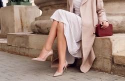 Closeup fashionable woman legs wear beige high heel shoes, dress and sitting. Outdoor fall and spring outfit