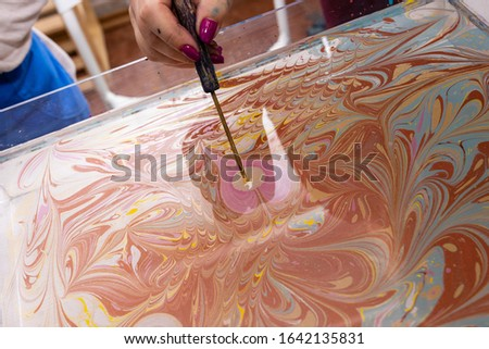 """closeup female hand creates a pattern of paints on the surface of the water with a special tool. Ebru Art, the Ancient Techniques of """"Painting on Water"""""""