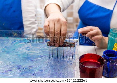 """closeup female hand forms a pattern of paints on the surface of the water with the help of a special tool - combs. Ebru Art, the Ancient Techniques of """"Painting on Water"""""""