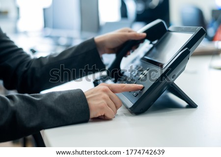 Closeup female hand on landline phone in office. Faceless woman in a suit works as a receptionist answering the phone to customer calls.