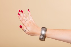 Closeup female hand, woman showing fashionable accessories bijouterie armlet and rings on finger. Beauty red nails.