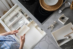 Closeup female hands neatly assembling cutlery in storage pp boxes at drawer of modern minimalistic kitchen. Woman placing fork, spoon and knife into cuisine cupboard. General cleaning, tidying up