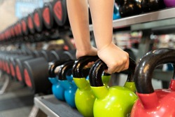 Closeup female hands pick up kettlebell from the set of dumbbell for exercise and strength training. sport, fitness, health, lifestyle and people concept