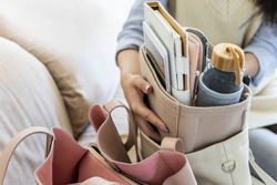 Closeup female hands shifting modern comfortable storage felt organizer into leather handbag. Concept of comfy keeping, carrying or moving personal accessories into woman bag. Getting ready equipment
