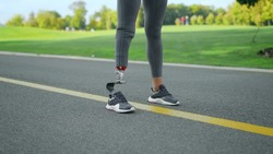 Closeup female jogger with artificial limb standing in park. Athletic woman runner in sportswear at start position on road. Sportswoman prosthetic leg with preparing to run outdoors in slow motion