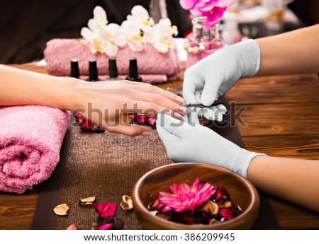 Closeup finger nail care by manicure specialist in beauty salon.  #386209945