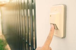 Closeup Finger of man pressing doorbell home.