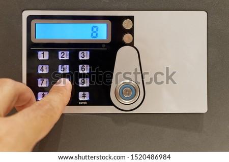Closeup finger touching keypad of digital safe #1520486984