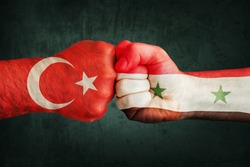 Closeup, flags on fist of Turkey against Syria on a black wall background. Concept of crisis of war and political conflicts between nations.