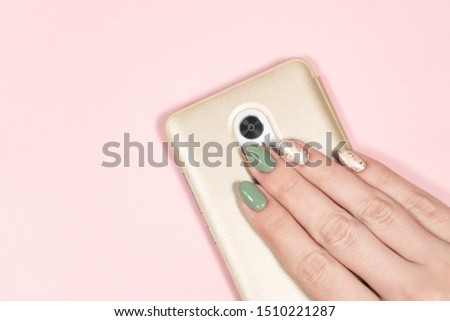 Closeup flatlay top view photography of beautiful one female hand holding modern smartphone in golden case isolated on pink pastel background. Trendy 2 colors green and beige glamourous manicure.