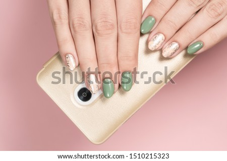 Closeup flatlay top view photography of beautiful two female hands holding modern smartphone in golden case isolated on pink pastel background. Trendy 2 colors green and beige glamourous manicure.