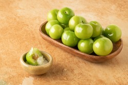 closeup fresh and ripe green plums on a table served with salt to dip them
