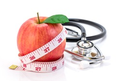 Closeup fresh fuji pink lady apple fruit  with measuring tape and medical stethoscope isolated on white background. Healthy eating, weight loss,slimming and dieting conceptual.