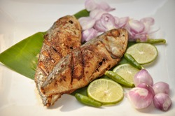Closeup Fried fish in plate serve with lime,onion,chilli slice It is homemade food from the kitchen at home. Ketone Diet for weight Loss.