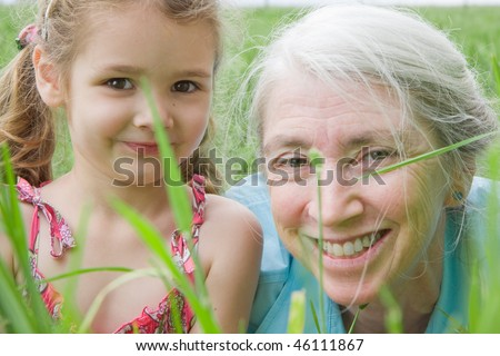 Closeup girl and her grandmother in long grass