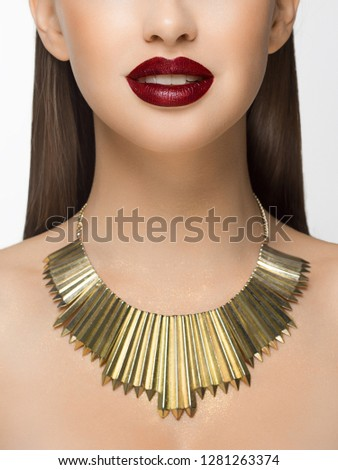 Closeup glamorous image of female predator with licking red lips. On the neck of the girl gold jewelry and sparkles on the body. Beautiful transparent skin. Spa care or beauty care. Beauty sexy woman